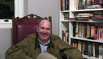 Thumbnail of Lourens Ackermann sitting in a high backed chair next to a bookshelf with a partial window in the background.
