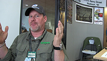 Thumbnail of Craig Amacker sitting front of a booth at a fishing Expo.