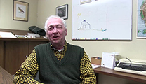 Thumbnail of Frank Amato sitting in a office with a typewriter and a whiteboard in the background.