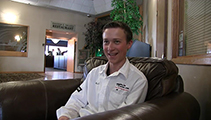 Thumbnail of Alex Assante sitting in a large arm chair at a hotel hosting the East Idaho Fly Tiers Expo in Idaho Falls, ID, people walk by in the background.