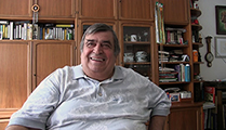 Thumbnail of Theo Atanasov sitting in his office with bookshelves in the background.