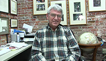 Thumbnail of John Bailey sitting in a brick office surrounded by pictures on the walls and a globe behind him.