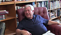 Thumbnail of Alen Baker sitting in red arm chair with shelves and rows of books in back ground.