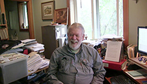 Thumbnail of Bill Bakke is sitting in his home office surrounded by research material and computer to the right.