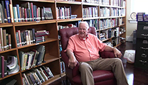 Thumbnail of Ron Beane sitting in red arm chair with rows and shelves of book behind him.