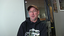 Thumbnail of Randy Berndt sitting front of a booth at a fishing Expo.