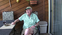 Thumbnail of A. K. Best sitting on porch with table to his right.