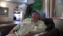 Thumbnail of Dave Brackett sitting in a large arm chair at a hotel hosting the East Idaho Fly Tiers Expo in Idaho Falls, ID, people walk by in the background.