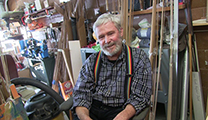 Thumbnail of Glenn Brackett is sitting in his workshop surrounded by materials and tools of his trade in making bamboo rods.