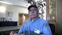 Thumbnail of Jay Buchner sitting in a large arm chair at a hotel hosting the East Idaho Fly Tiers Expo in Idaho Falls, ID, people walk by in the background.