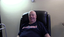 Thumbnail of Tom Bugni sitting in a large arm chair with a white wall in the background and a walker on the left partially cutoff..