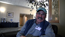 Thumbnail of Joe Burke sitting in a large arm chair at a hotel hosting the East Idaho Fly Tiers Expo in Idaho Falls, ID, people walk by in the background.