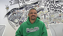 Thumbnail of Matthew Burkett sitting with a complex mural in the background.