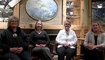 Thumbnail of four women sitting in a semi circle a painting and figurines on shelves in the background.