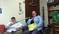 Thumbnail of Floyd and Janet Dean sitting in an office with a door and bookcase in the background.