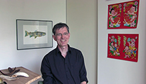 Thumbnail of Peer Doering-Arjes sitting in a corner with several artworks in the background.