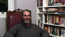 Thumbnail of Stephen Dugmore sitting in a high backed chair next to a bookshelf with a partial window in the background.