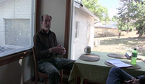 Thumbnail of Ed Engle sitting in his dining room backlite by two windows on either side of him looking out at his yard.