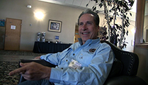 Thumbnail of Steve Fernandez sitting in a large arm chair at a hotel hosting the East Idaho Fly Tiers Expo in Idaho Falls, ID, people walk by in the background.