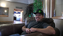 Thumbnail of Tanner Flake sitting in a large arm chair at a hotel hosting the East Idaho Fly Tiers Expo in Idaho Falls, ID, people walk by in the background.