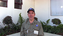 Thumbnail of Andrew Fowler sitting outside in a corner with plants and windows in the background.