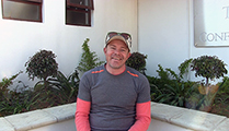 Thumbnail of Darren Fowler sitting outside in a corner with plants and windows in the background.