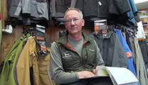 Thumbnail of Jimmy Gabettas sitting in his outfitting store Jimmy's All Seasons Angler in Idaho Falls, Idaho, merchandise is being displayed in the background.