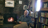 Thumbnail of John Gierach sitting in front of a fireplace and a bookshelf.