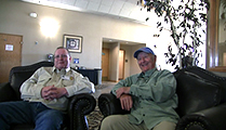 Thumbnail of Ben and Buck Goodrich sitting in a large arm chairs at a hotel hosting the East Idaho Fly Tiers Expo in Idaho Falls, ID, people walk by in the background.