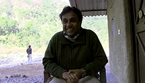 Thumbnail of Chandan Gupta sitting under an overhang in shadow next to a building surrounded lush greenery behind him.
