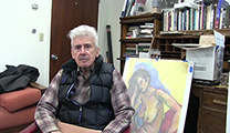 Thumbnail of Joe Gutkoski sitting with a book in his lap and a door over one shoulder and an original art work over his other shoulder.