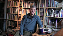 Thumbnail of Rick Hafele sitting in front of large bookshelf full of books.