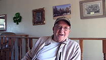 Thumbnail of Monty Hankinson sitting in his house with a wall full of pictures on it and a wooden railing in the background.