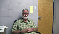 Thumbnail of Bud Heintz sitting with a closed door and concrete wall in the background.