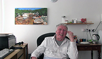 Thumbnail of Edward Herbst sitting in a chair and pictures hanging on the wallwith other clutter on a desk behind him.