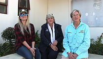 Thumbnail of Marlize Heyns, Renthia de Wood, Marietjie Davies sitting outside in a corner with plants and windows in the background.