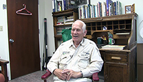 Thumbnail of Henry Hoffman sitting in an office with a closed door, bookcase, and desk in the background.