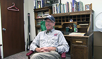 Thumbnail of Mac Huff sitting in an office with a closed door, bookcase, and desk in the background.