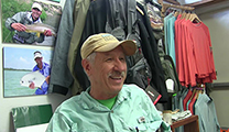 Thumbnail of Bruce James sitting before merchandise and photographs in Grand Teton Fly Fishing in Jackson Hole, WY.