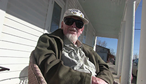 Thumbnail of Bud Lilly sitting on a porch outside a white building in the sun.