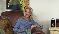 Thumbnail of AD Maddox sitting in leather arm chair with a partial piece of her artwork in the background.