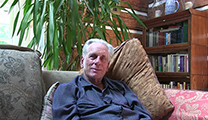 Thumbnail of Tom McGuane sitting on a couch with a bookshelf and a palm plant in the background.