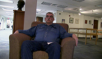 Thumbnail of Daniel D. McKinney sitting the Montana State University  Merrill G. Burlingame Special Collections Reading Room.
