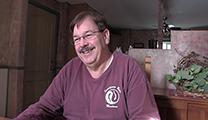 Thumbnail of Gregg Messel sitting in his house with a plant a partition in the background.