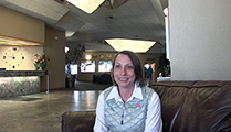 Thumbnail of Carrie Morgan sitting in a large arm chair at a hotel hosting the East Idaho Fly Tiers Expo in Idaho Falls, ID, people walk by in the background.