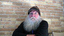 Thumbnail of Tim Mosolf sitting in front of a brickwall, he has a full white beard and is wearing a hat.