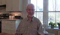 Thumbnail of Rich Norman sitting in a kitchen with a large window behind him.