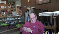 Thumbnail of Richard Parks siting in his fly shop, Park's Fly Shop in Gardiner, MT.