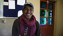 Thumbnail of Sanjeev Paroiya sitting in front of bulletin board with a door behind him.