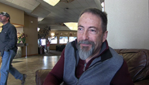 Thumbnail of Joe Pehrson sitting in a large arm chair at a hotel hosting the East Idaho Fly Tiers Expo in Idaho Falls, ID, people walk by in the background.